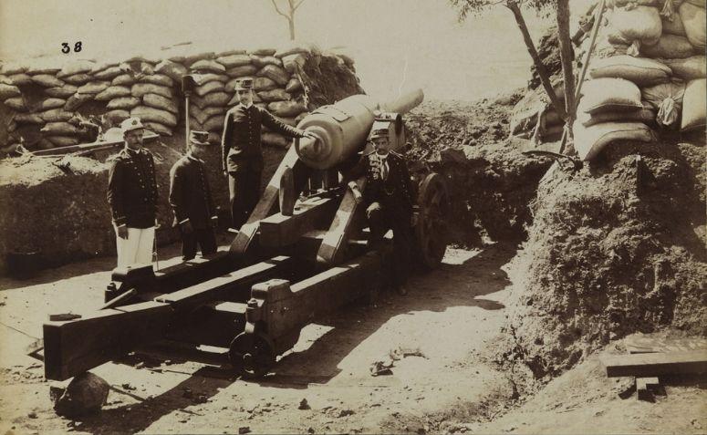 Marinheiros ao lado de um canhão.