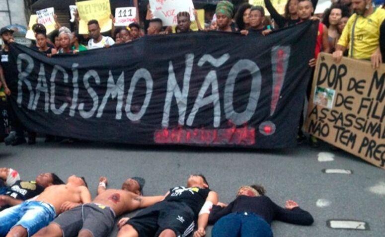 """Um ato organizado pelo movimento negro, segurando uma faixa escrito """"racismo não!"""""""